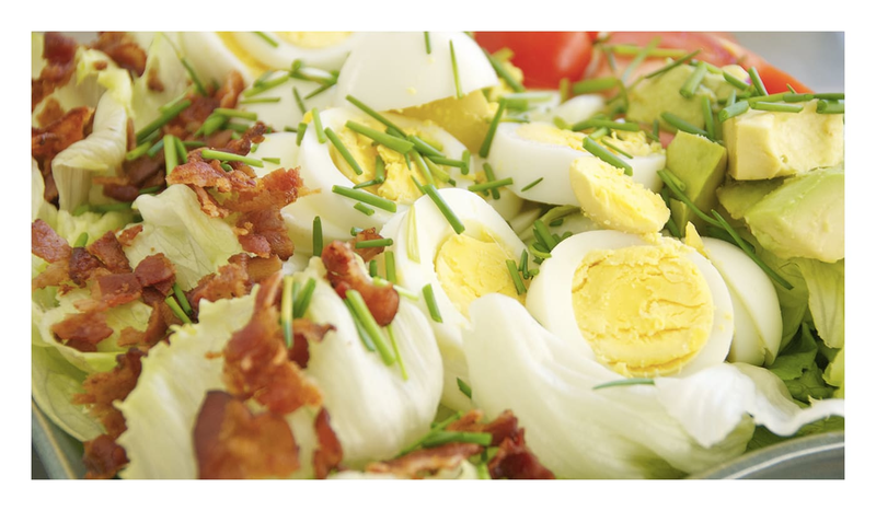 An up-close image of a Cobb salad, with bacon, hard boiled eggs and avocado